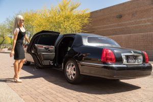 Attractive female driver, wearing sunglasses, holding open the driver side rear door of our stretch limousine in Phoenix