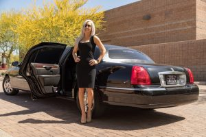 Attractive female driver, wearing sunglasses, standing beside the open driver side rear door of our stretch limo in Phoenix