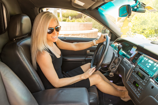 Attractive blond woman in a black dress and sunglasses, smiling at the camera, sitting in the driver's seat of a black limousine symbolizing our Executive Limousine and Sedan in Phoenix, AZ