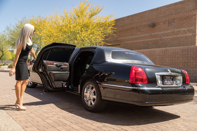 Attractive blond woman in a black dress and sunglasses holding the rear driver's side door open of a black limousine symbolizing our First Class Executive Limo in Phoenix, AZ
