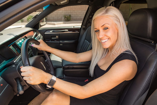 Attractive blond woman in a black dress, smiling at the camera, sitting in the driver's seat of a black limousine symbolizing our Luxury Car Hire Services in Phoenix, AZ