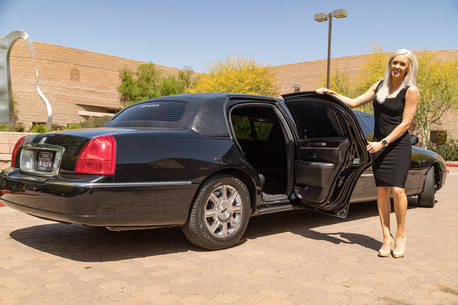 Attractive blond woman in a black dress and sunglasses, smiling holding open the rear passenger side door of a black limousine symbolizing our Upscale Executive Transportation in Phoenix, AZ
