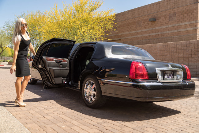 Attractive blond woman in a black dress holding open the door of a black limousine symbolizing our Corporate Transportation Services in Phoenix, AZ