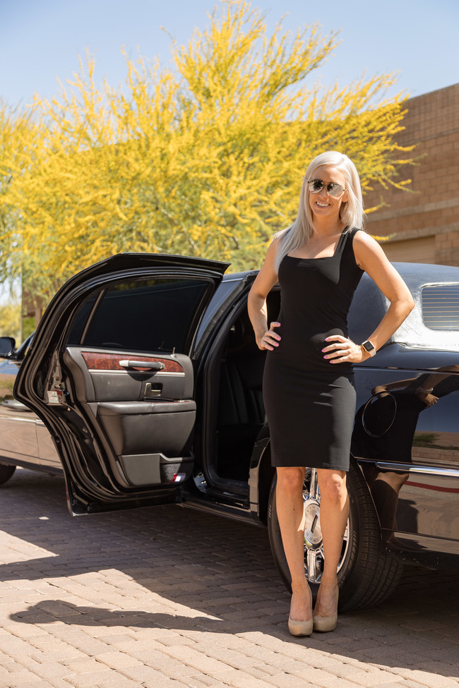 Attractive blond woman in a black dress and sunglasses, with her hands on her hips, standing next to the rear open door of a black limousine symbolizing our Corporate Transportation Solutions in Phoenix, AZ