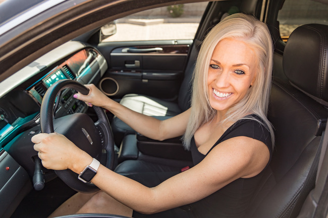 Attractive blond woman in a black dress sitting in the driver's seat of a black limousine, smiling, symbolizing our Corporate Travel Car Service in Phoenix, AZ