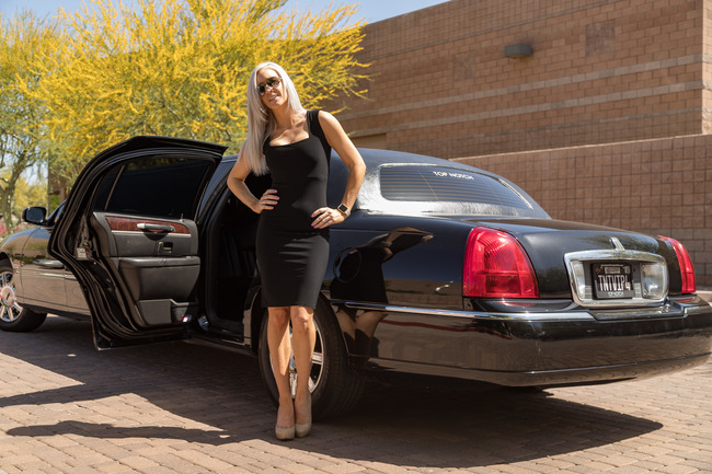 Attractive blond woman in a black dress and sunglasses, with her hands on her hips, standing next to the rear open door of a black limousine symbolizing our Corporate VIP Transportation in Phoenix, AZ