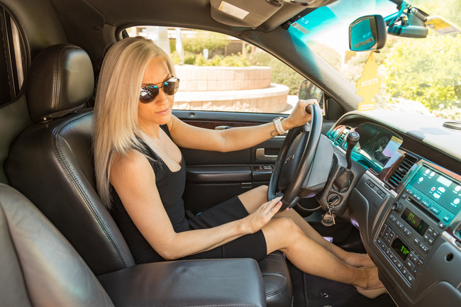 Attractive blond woman in a black dress and sunglasses, smiling, sitting in the driver's seat of a black limousine symbolizing our Executive Limo Hire in Phoenix, AZ