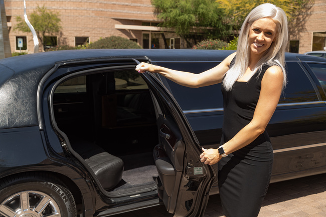 Attractive blond woman in a black dress holding open the rear passenger side door of a black limousine symbolizing our Executive Limo Service in Phoenix, AZ